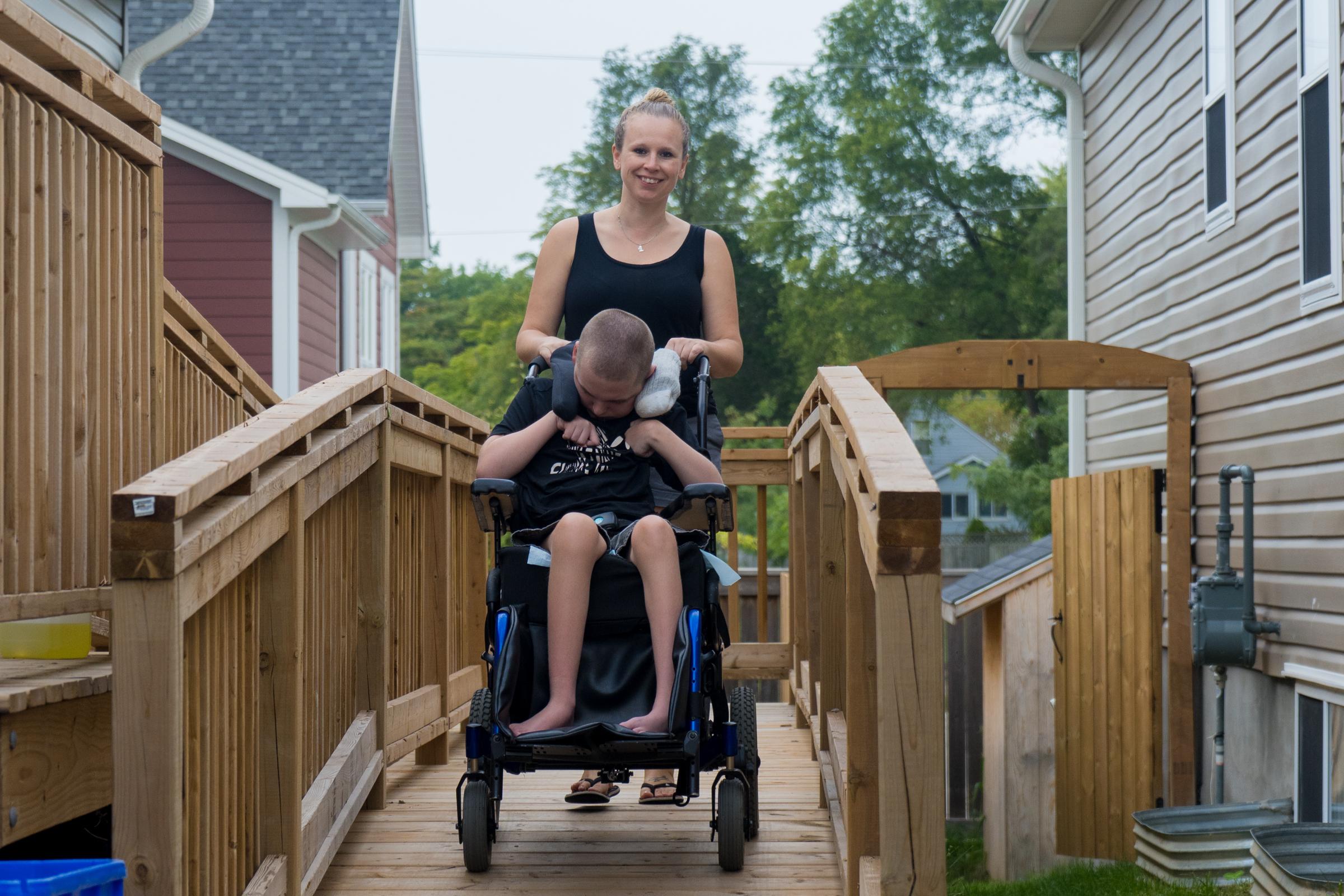 Brianne taking her son Brayden down the wheelchair ramp on their Habitat home.