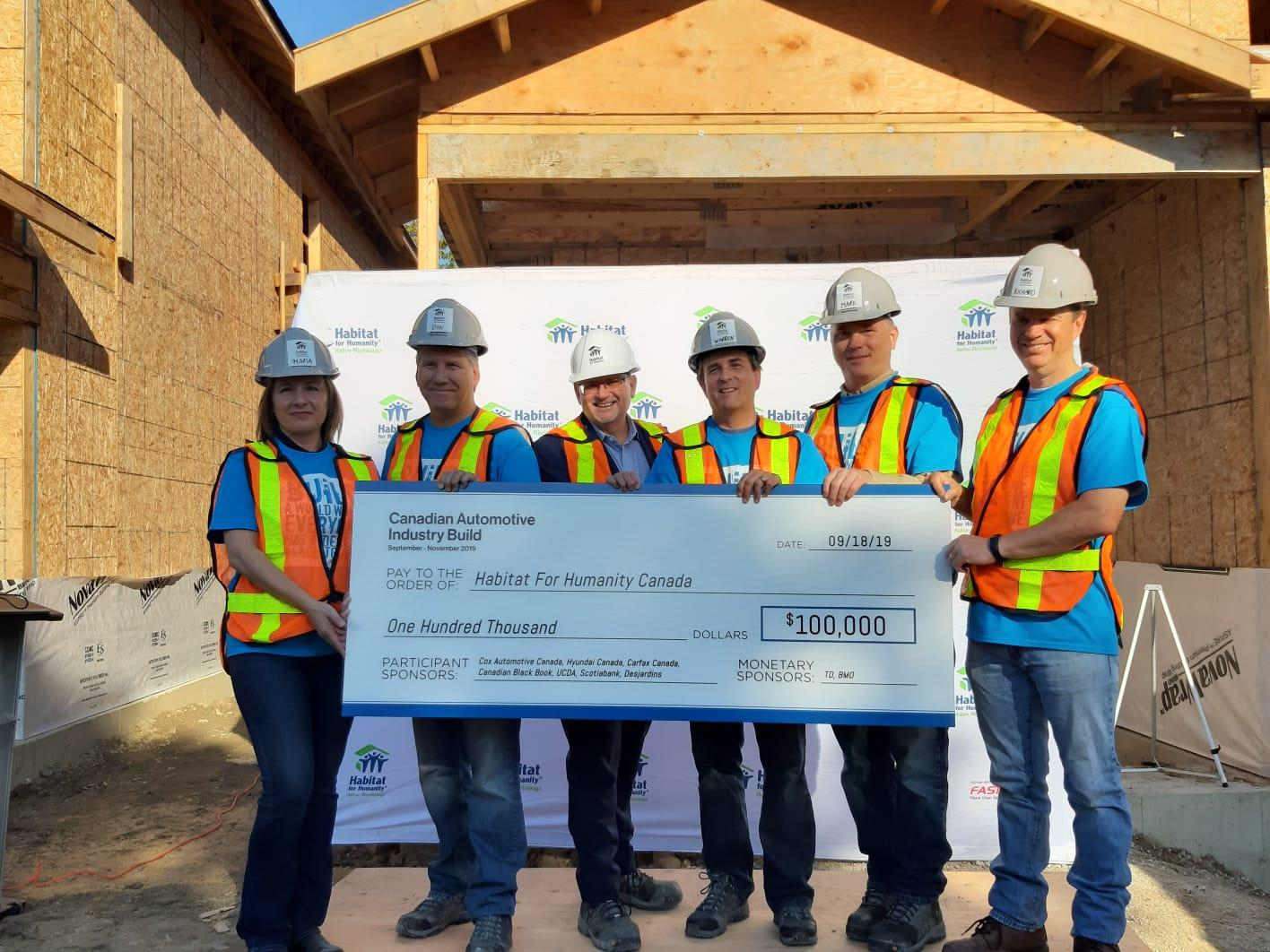 Habitat Canada President and CEO, Mark Rodgers, holds cheque from Canadian Automotive Industry Build partners