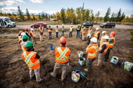 Volunteer standing in a circle with safety vests and hard hats