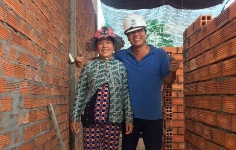 Habitat Vietnam homeowners Trang and Van stand in their partially constructed Habitat home.